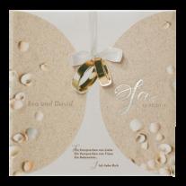 Stilvolle Hochzeitseinladung in transparentem Umschlag mit Sand und Muscheln