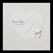 Zierliche Hochzeitseinladung auf Perlmuttpapier mit Herzmotiv